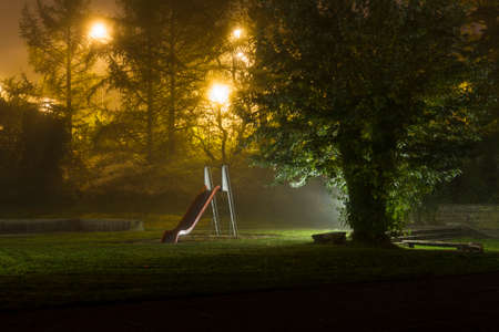 An empty playground with a red slide at night with fog and creepy atmosphere Stock Photo
