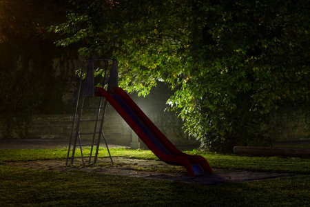 maniac: An empty playground with a red slide at night with fog and creepy atmosphere Stock Photo