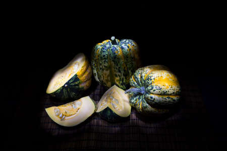 Green, yellow and white speckled delicious and fresh gorgonzola pumpkins on black background. One of the pumpkins is cut into three pieces showing the seeds.