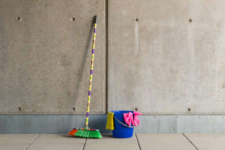 the daily grind: Colorful cleaning equipment (broom, bucket, rag and gloves) in front of a gray, monotonous concrete wall and stained floor.