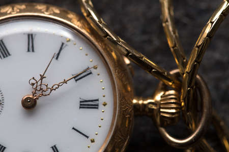 Closeup of an old small golden pocket watch on grey felt