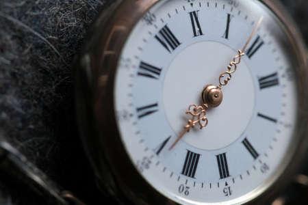 cypher: Closeup of an old small bronze pocket watch on grey felt