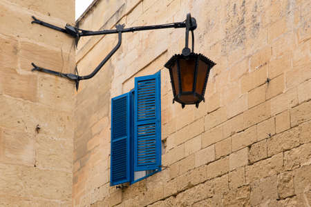 window panes: A narrow street in the historical medieval city of Mdina on Malta. View on blue window panes and a street lamp.