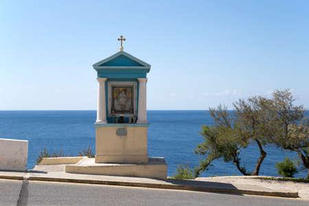 A small blue catholic shrine on the roadside close to the coast on Malta.