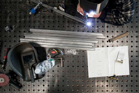 metal worker: A metal worker welding different metal parts on a table according instructions. Stock Photo