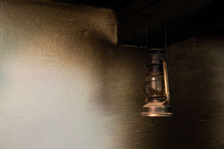 smut: Vintage petroleum lamp hanging from the ceiling in a kitchen with smoke stains on the wall Stock Photo