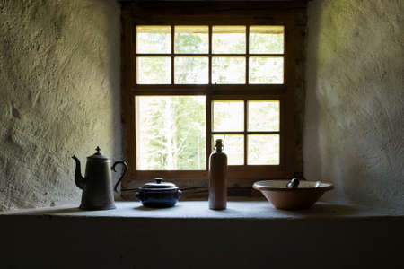 View on several vintage household items standing close a somber window sill.