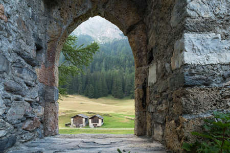 View through the empty doorway arch of an ancient castle ruin on two huts. Green forest and meadow visible in the background.