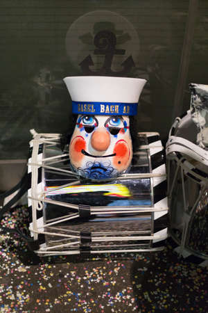 snare drum: A single mask representing a sailor with orange cheeks and nose laying on top of a snare drum during the Basel carnival. Picture taken on 15th of February 2016 in Basel, Switzerland