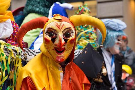 fasnacht: A participant of the basel carnival disguised as a harlequin clown in red and yellow costume looks directly into the camera. Picture taken on 16th of February 2016 in the Freie Strasse in Basel, Switzerland
