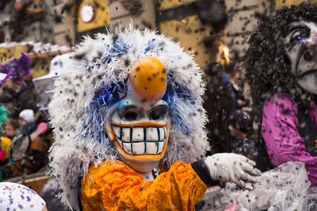 A waggis (a typical character of the Basel carnival) in yellow white costume throwing confetti into the crowd. Picture taken on 16th of February 2016 in the Freie Strasse in Basel, Switzerland