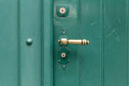 key holes: A green painted wooden door with a bronze door handle and two key holes.