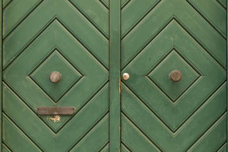 A green painted wooden double door with diamond pattern and round door knob. The left door side has a slit for mail.