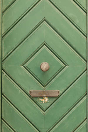 A green painted wooden door with diamond pattern, round door knob and a mail box. Stock Photo