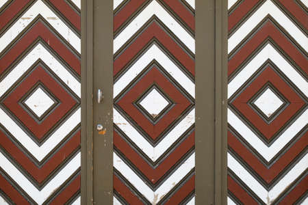 A wooden garage door with diamond pattern painted in brown, white and red color