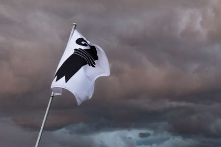 A single flag of Basel in Switzerland in front of a gloomy sky. Dark storm clouds loom in the background.