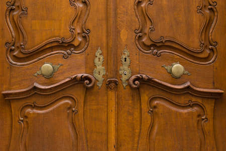 key holes: Beautifully carved wooden door with metal door knobs and decorated key holes.