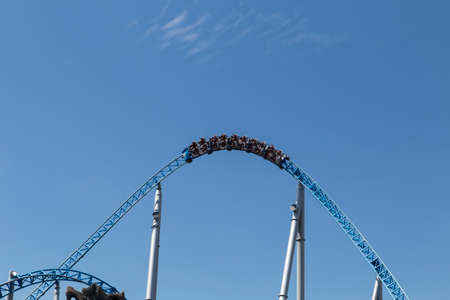 Blue roller coaster loop with cart in front of blue sky