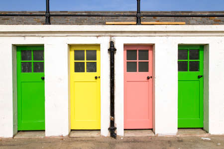 identical: A storage house with white walls and colored narrow doors in plain sunlight