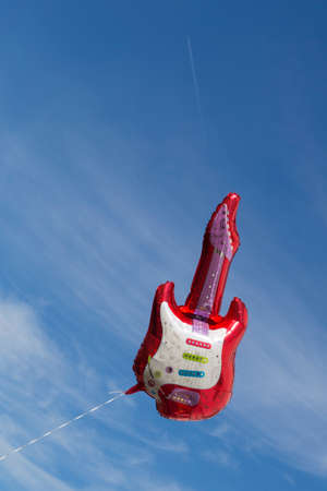A red air balloon shaped like an electric guitar floating in the blue sky. Stock Photo