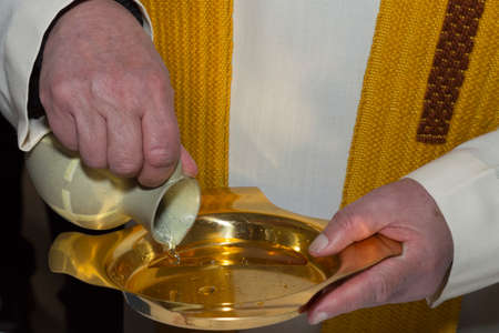 priest's ritual robes: A priest pours holy water from a ceramic jug into a golden plate during a christening ritual