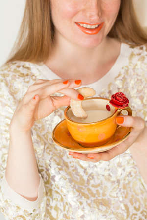A woman with orange lipstick enjoys drinking milk from a beautiful handmade orange cup with red rose and eating a cookie
