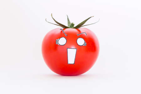 A single fresh red tomato with scared face in front of white background
