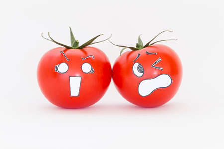 Two fresh red tomatoes with scared faces in front of white background Stock Photo