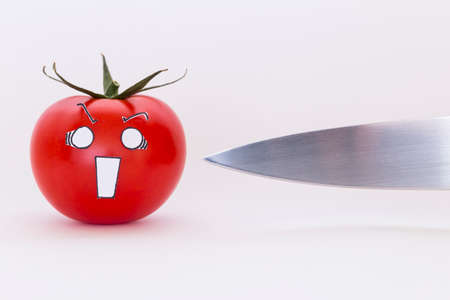 A fresh red tomato with scared face and a sharp knife in front of white background Stock Photo