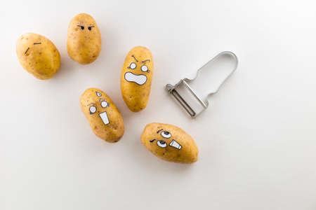 Fresh potatoes with cartoon style faces laying on white surface are scared from a peeler Stock Photo