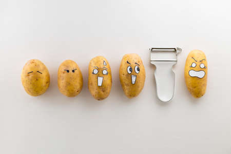 panicked: Fresh potatoes with cartoon style faces laying on white surface are scared from a peeler Stock Photo