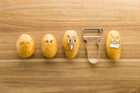 Fresh potatoes with cartoon style faces laying on a brown cutting board and scared to death from a peeler