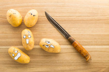 Fresh potatoes with cartoon style faces laying on a brown cutting board and scared to death from a knife