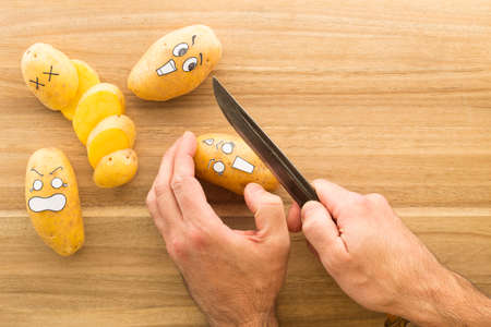panicked: a fresh potato with cartoon style face scared to death while being held in one hand. The other hand holds a big knife Stock Photo