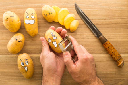 panicked: Fresh potatoes with cartoon style faces laying on a brown cutting board and scared to death from a knife. One potato is being peeled.