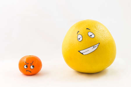 predominance: A big yellow honey pomelo and a tangerine with funny faces and white background