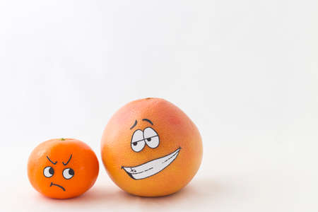 predominance: A big orange grapefruit and a tangerine with funny faces and white background