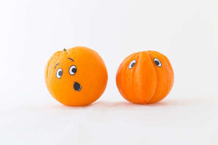Fresh oranges with funny faces in front of white background. One orange has a huge nose Stock Photo