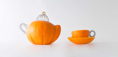 Funny tea cup and pot made from fresh oranges in front of white background