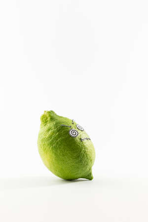 A fresh green lemon with sour looking cartoon style face on white background Stock Photo
