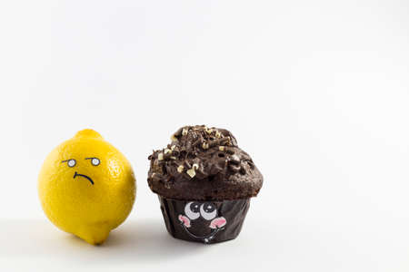 A sweet chocolate muffin and fresh lemon with cartoon style faces on white background opposing each other Stock Photo