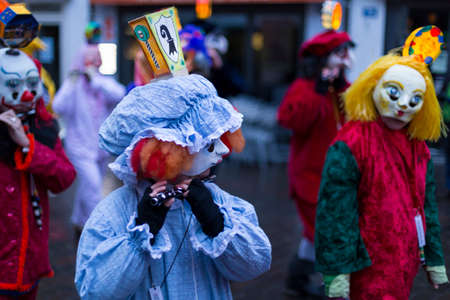 Basel carnival. Ruemelinsplatz, Basel, Switzerland - March 6, 2017. Close-up of a group of carnival participants in their individual costumes and masks playing piccolo and marching through the streets of the old town during the Morgestraich parade.