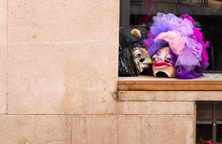 Basel carnival. Gruenpfahlgasse, Basel, Switzerland - March 7, 2017. Closeup of two carnival masks resting on the window sill outside of a restaurant.