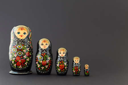 matroshka: Beautiful black matryoshka dolls with white, green and red painting in front of dark background