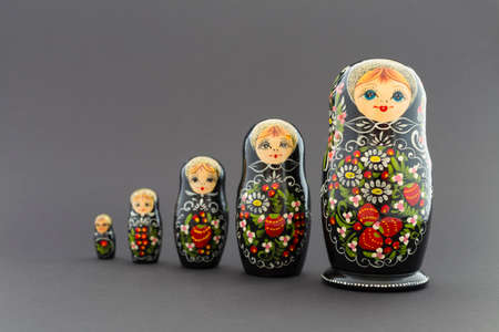 muñecas rusas: Beautiful black matryoshka dolls with white, green and red painting in front of dark background