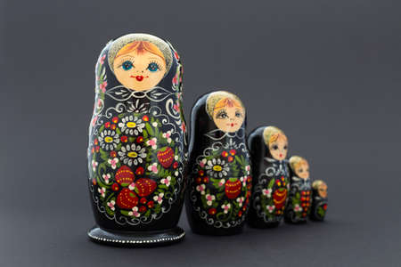 Beautiful black matryoshka dolls with white, green and red painting in front of dark background