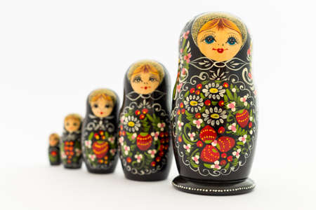 Beautiful black matryoshka dolls with white, green and red painting in front of light background