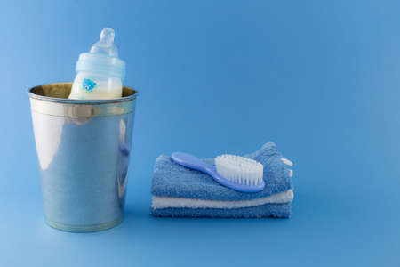 Baby boy luxurious items collection isolated on pale blue background. A milk bottle in a luxurious silver champagne bucket. A hairbrush on a stack of towels.