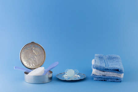 princely: Baby boy luxurious items collection isolated on pale blue background. Hairbrush and comb in a silver can, pacifier on a silver plate and towels. Stock Photo
