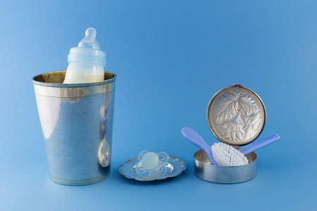 princely: Baby boy luxurious items collection isolated on pale blue background. Milk bottle in a luxurious silver champagne bucket, a pacifier on a silver plate and a hairbrush and comb in a silver can.